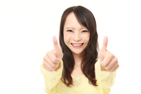 43844020 - young japanese woman with thumbs up gesture